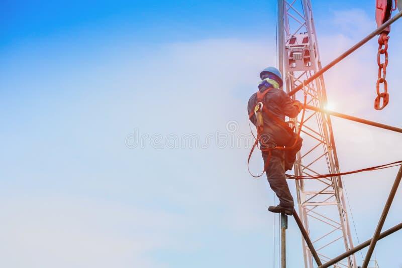 Arbeiten an hith mit Baugerüst mit der Ausrüstung schützend auf Kranhintergrund für Sicherheitskonzept lizenzfreie stockbilder