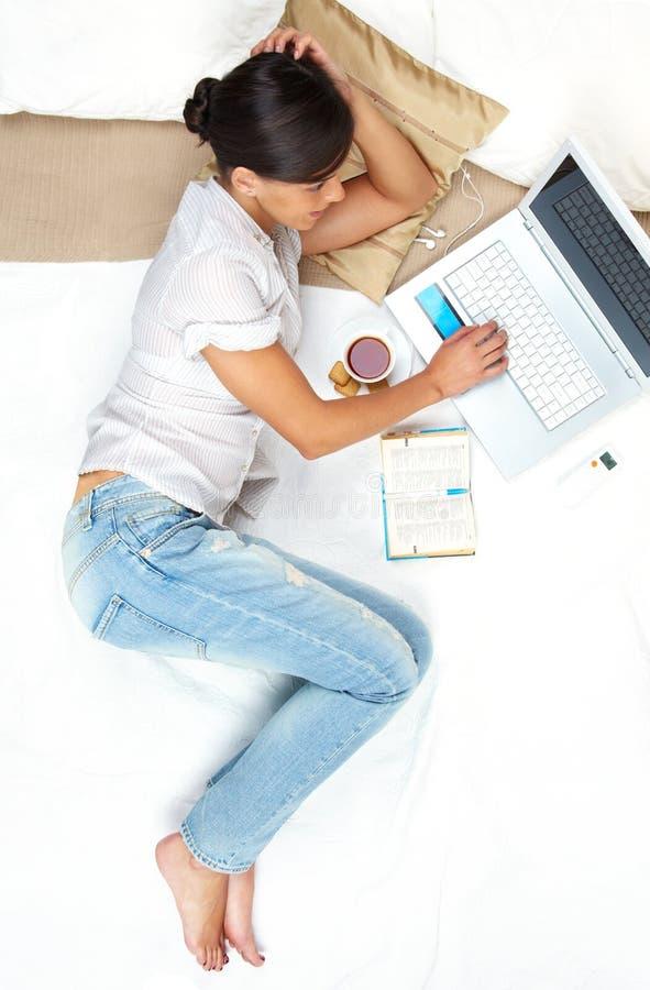 Arbeiten im Bett lizenzfreie stockbilder