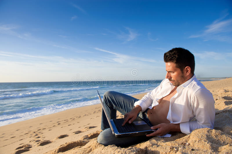Arbeiten im Laptop am Strand stockfoto