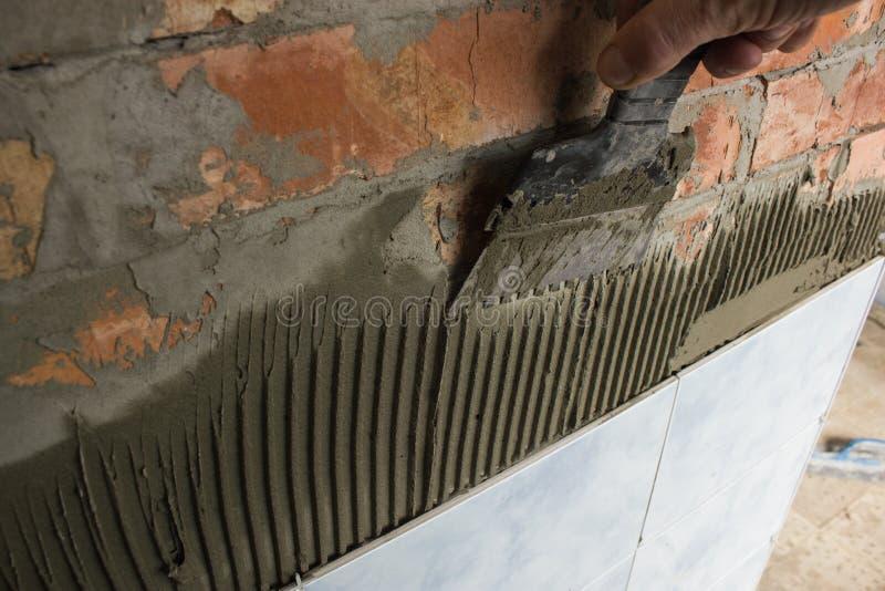 Arbeiten mit dem Mörser, der eine Badezimmerwand mit Ziegeln deckt stockbild