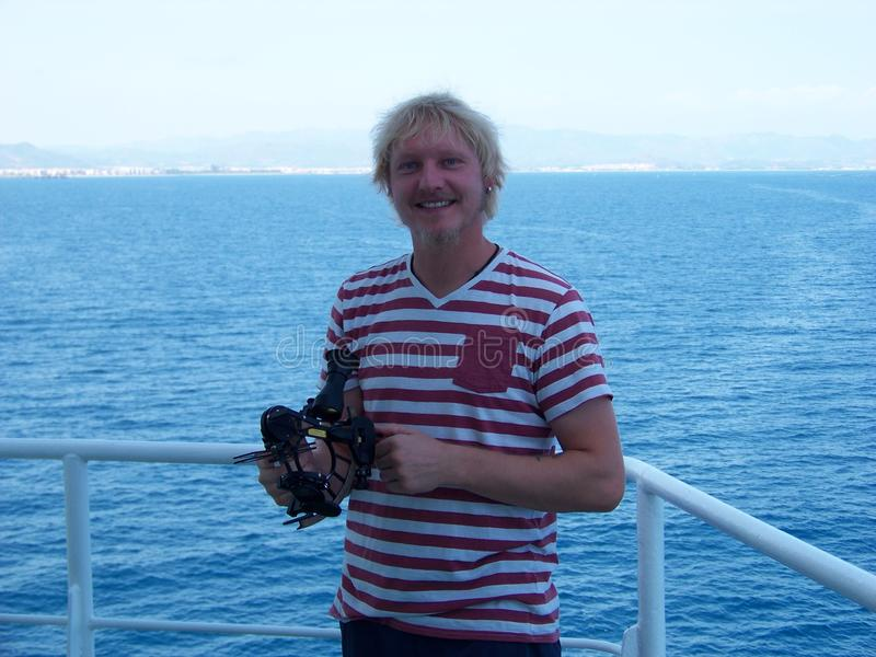 Arbeiten mit Sextanten an Bord von Handelsschiff nahe der Küste lizenzfreies stockfoto