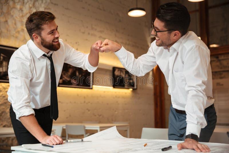 Arbeiten mit zwei erfolgreiches überzeugtes intelligenten Geschäftsmännern lizenzfreies stockfoto