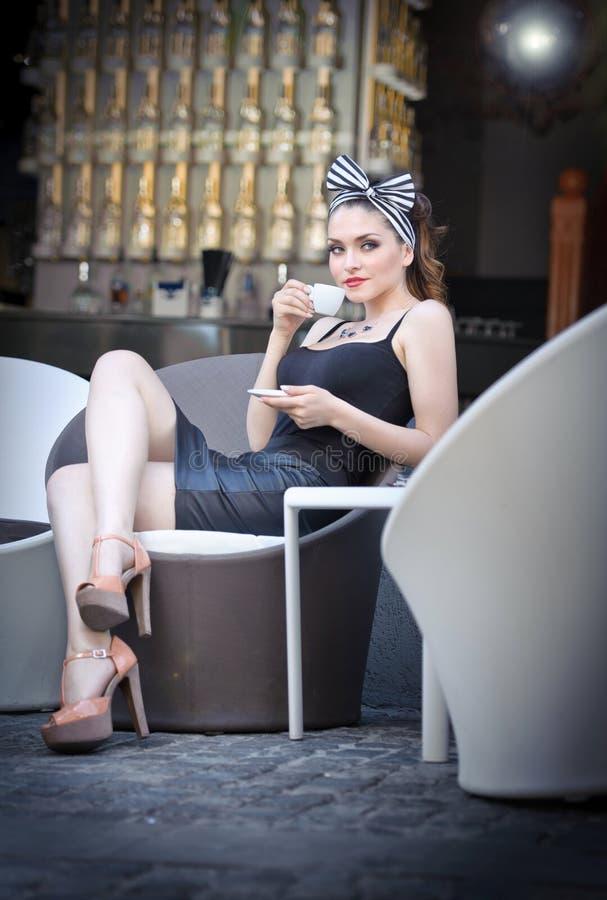 Arbeiten Sie attraktives Mädchen mit Tasse Kaffee in ihrem hand- im Freien auf Straße um. Retro- Schuss. Modekunstfoto sinnlicher  lizenzfreies stockbild