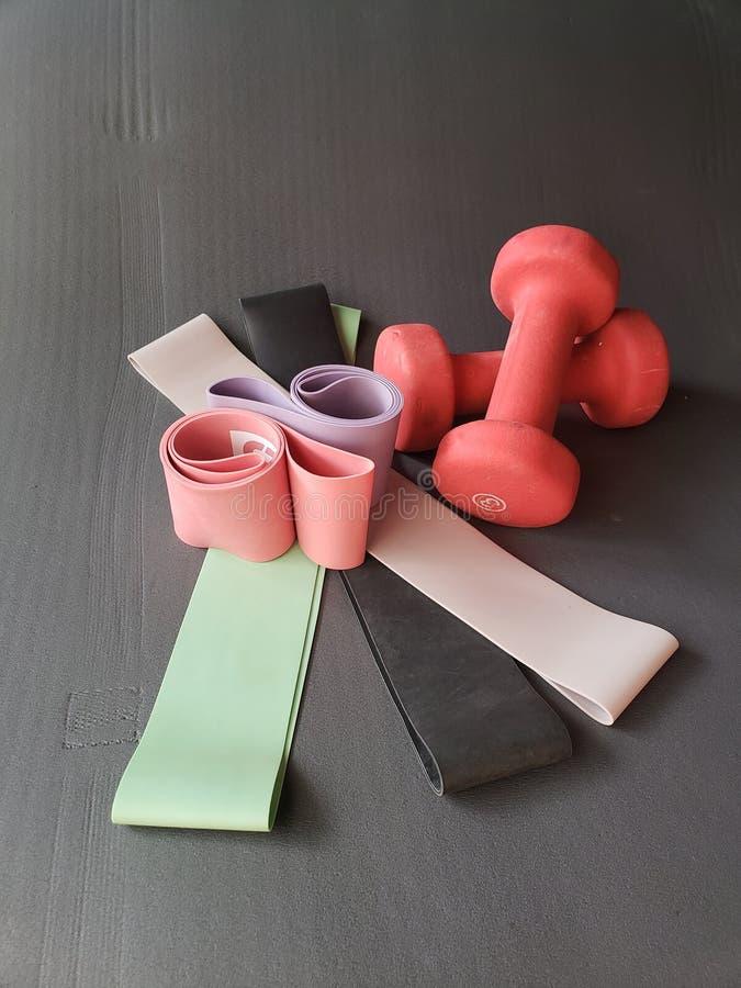 Arbeiten Sie Bänder und helle Gewichte auf Übungsmatte aus stockbilder