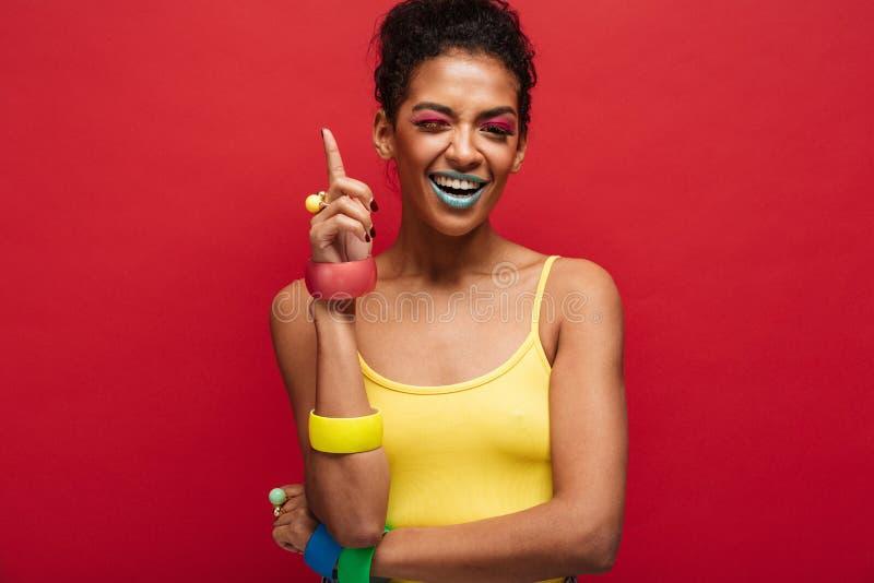 Arbeiten Sie Bild des weiblichen Modells des frohen Afroamerikaners im Gelb um stockfoto