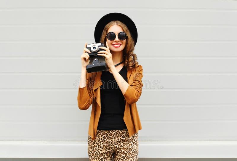 Arbeiten Sie Blick, recht kühles Modell der jungen Frau mit der Retro- Filmkamera um, die draußen einen eleganten Hut, braune Jac stockfoto