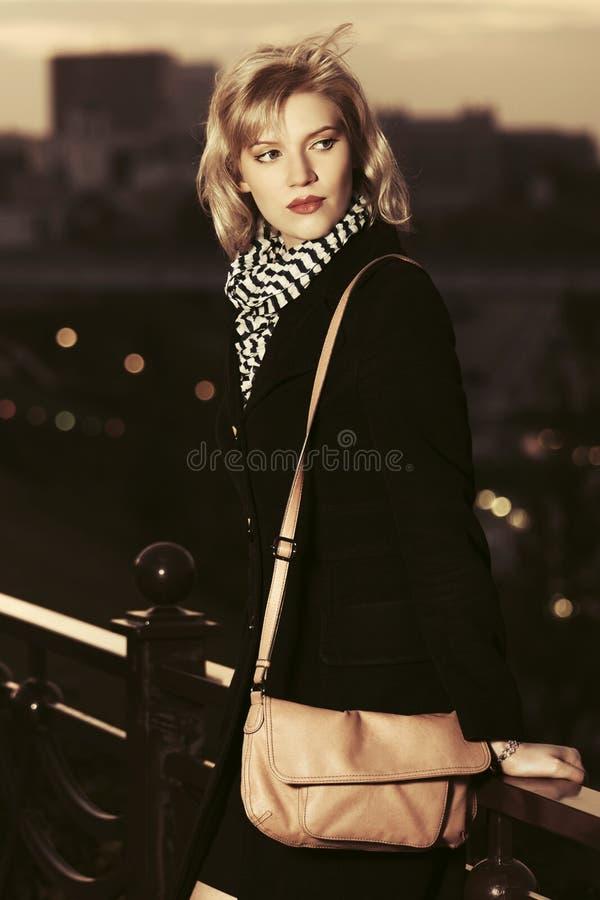 Arbeiten Sie blonde Frau im schwarzen Mantel mit der Handtasche um, die auf Zaun sich lehnt lizenzfreies stockbild