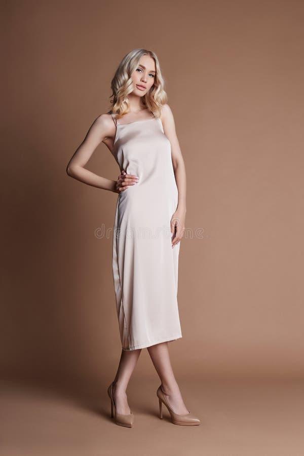 Arbeiten Sie Blondine in einem langen schönen Kleid um, das auf einem braunen Hintergrund aufwirft Schönes Haar und eine perfekte lizenzfreie stockfotos