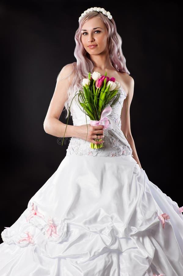 Arbeiten Sie Braut in einem Hochzeitskleid mit einem Blumenstrauß um stockbilder