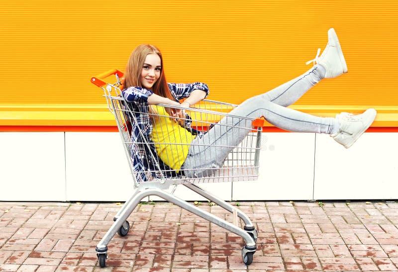 Arbeiten Sie das kühle Mädchen um, das den Spaß hat, der im Einkaufslaufkatzenwarenkorb sitzt stockbild