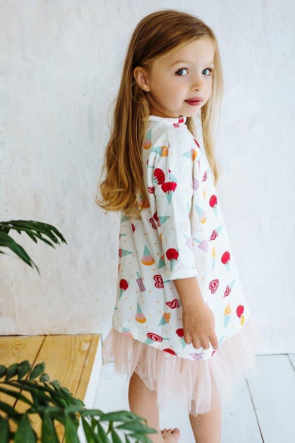 Arbeiten Sie das kleine Mädchen um, das im Kleid gegen bunte Wand aufwirft stockfotos