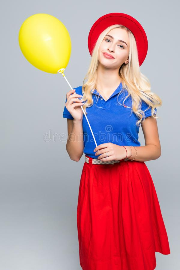Arbeiten Sie das Porträt von schönen jungen Frauen in der Farbkleidung und -hut um, die mit Ballons aufwirft, lokalisiert auf Wei lizenzfreies stockbild