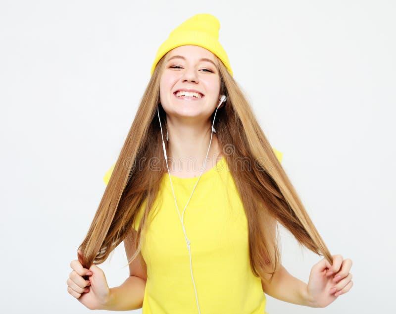 Arbeiten Sie das recht kühle Mädchen in den Kopfhörern hörend Musik um lizenzfreies stockfoto