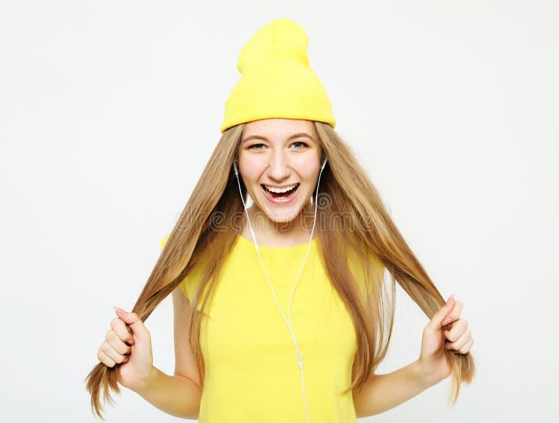 Arbeiten Sie das recht kühle Mädchen in den Kopfhörern hörend Musik um, die gelben Hut und T-Shirt trägt stockfotos