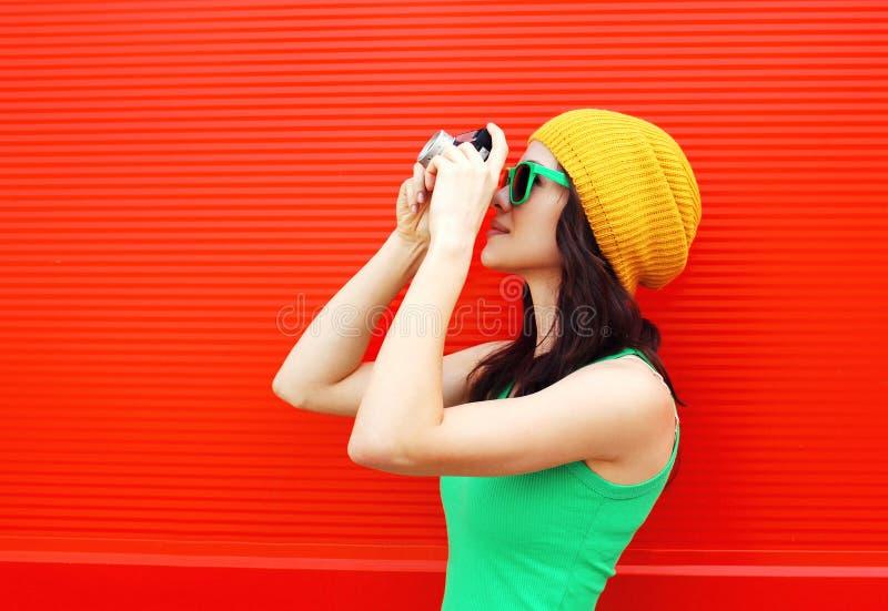 Arbeiten Sie das recht kühle Mädchen um, das bunte Kleidung mit Kamera trägt lizenzfreie stockfotografie