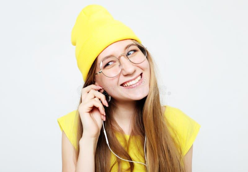 Arbeiten Sie das recht k?hle M?dchen in den Kopfh?rern h?rend Musik um, die gelben Hut und T-Shirt ?ber wei?em Hintergrund tr?gt lizenzfreies stockbild