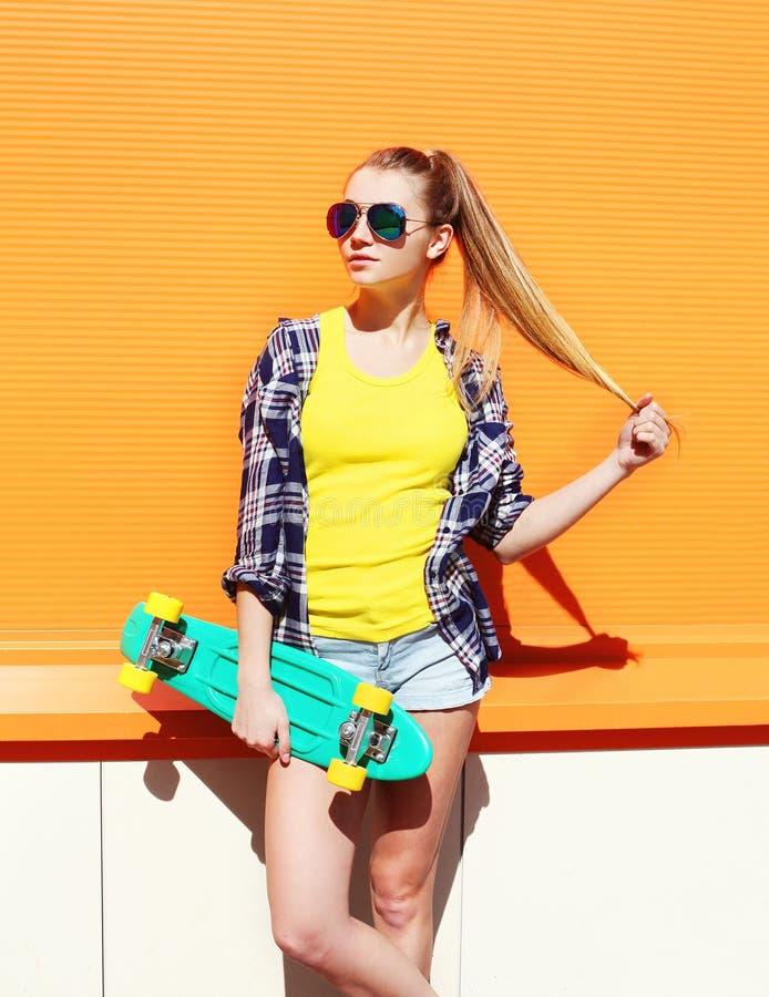 Arbeiten Sie dem hübschen Mädchentragen Sonnenbrille mit Skateboard über bunter Orange um stockfotografie