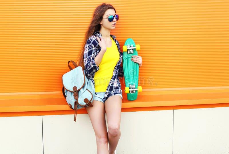 Arbeiten Sie dem recht kühlen Mädchentragen Sonnenbrille und Rucksack mit Skateboard über Orange um stockfoto