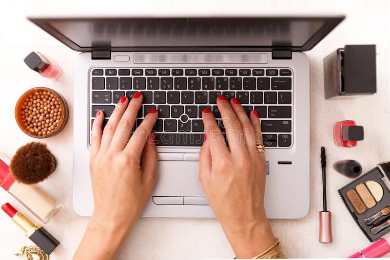 Arbeiten Sie den Blogger um, der am Schreibtisch mit einem Laptop arbeitet: Mode, Schönheit und Technologiekonzept lizenzfreie stockbilder