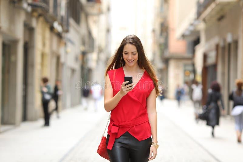 Arbeiten Sie die Frau um, die ein intelligentes Telefon geht und verwendet lizenzfreies stockfoto