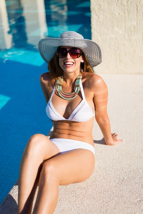 Arbeiten Sie die Frau um, die am Poolside auf Sommerferien sich entspannt lizenzfreie stockfotos