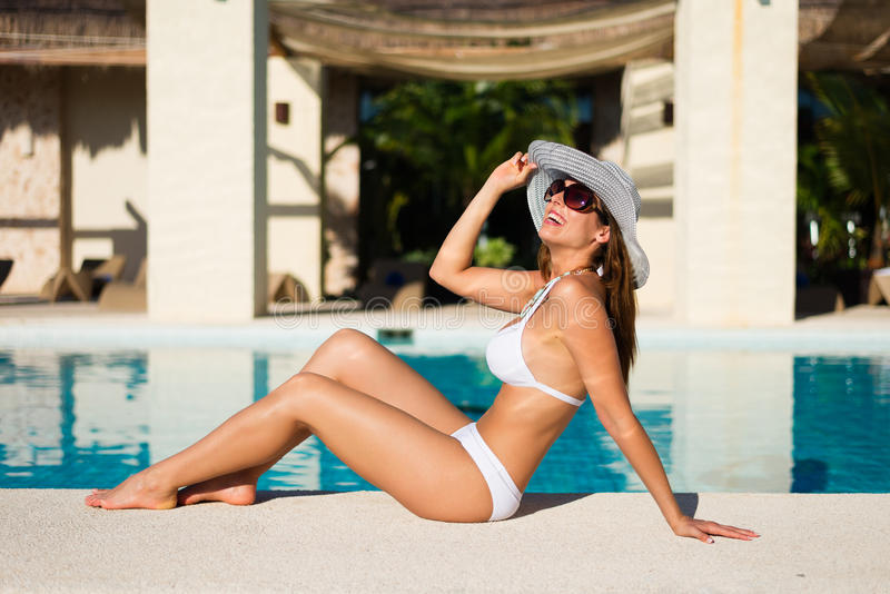 Arbeiten Sie die Frau um, die am Poolside auf Sommerferien sich entspannt lizenzfreies stockbild