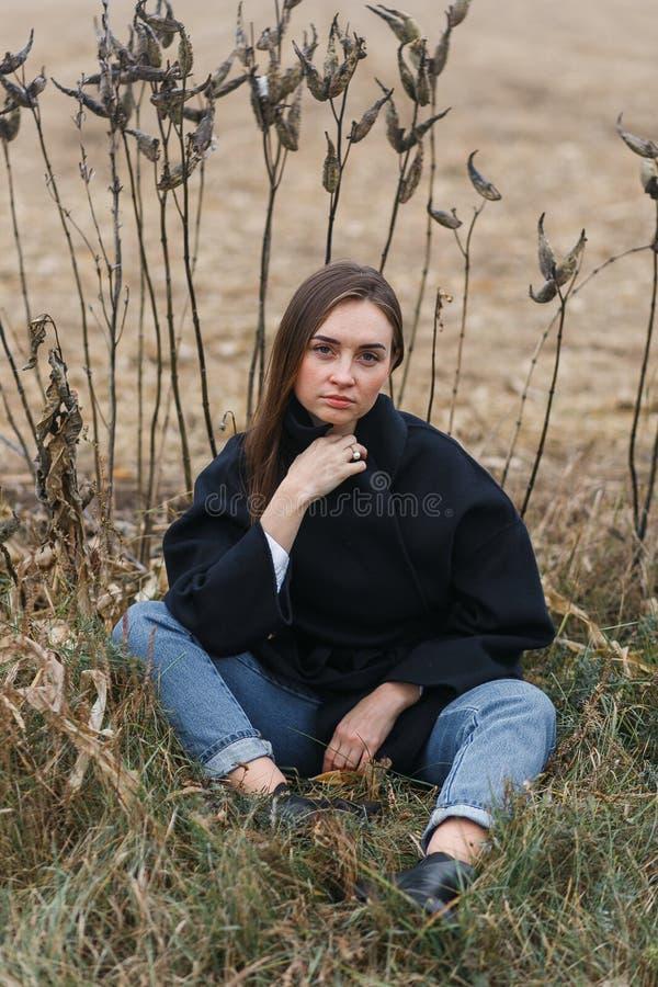 Arbeiten Sie die Frau um, die mit ungewöhnlichem Gras auf Hintergrund auf dem Herbstlandschaftsgebiet im Freien ist stockbilder