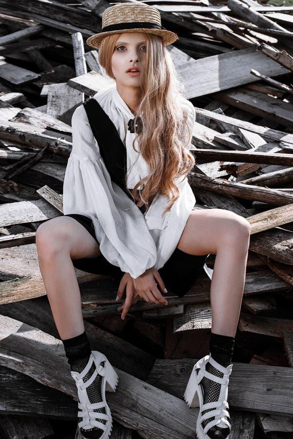 Arbeiten Sie die junge Frau um, die stilvolles Kleid und Strohhut an der Landschaft trägt Amische Modeart stockfotos