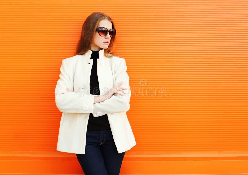 Arbeiten Sie die recht junge Frau um, die eine weiße Manteljacke gegen Orange trägt lizenzfreie stockfotografie