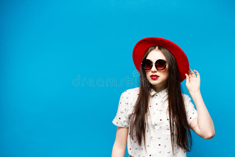 Arbeiten Sie die recht junge Frau um, die rote lipswearing Sonnenbrille eines schwarzen Hutes und roten Hut durchbrennt lizenzfreies stockbild