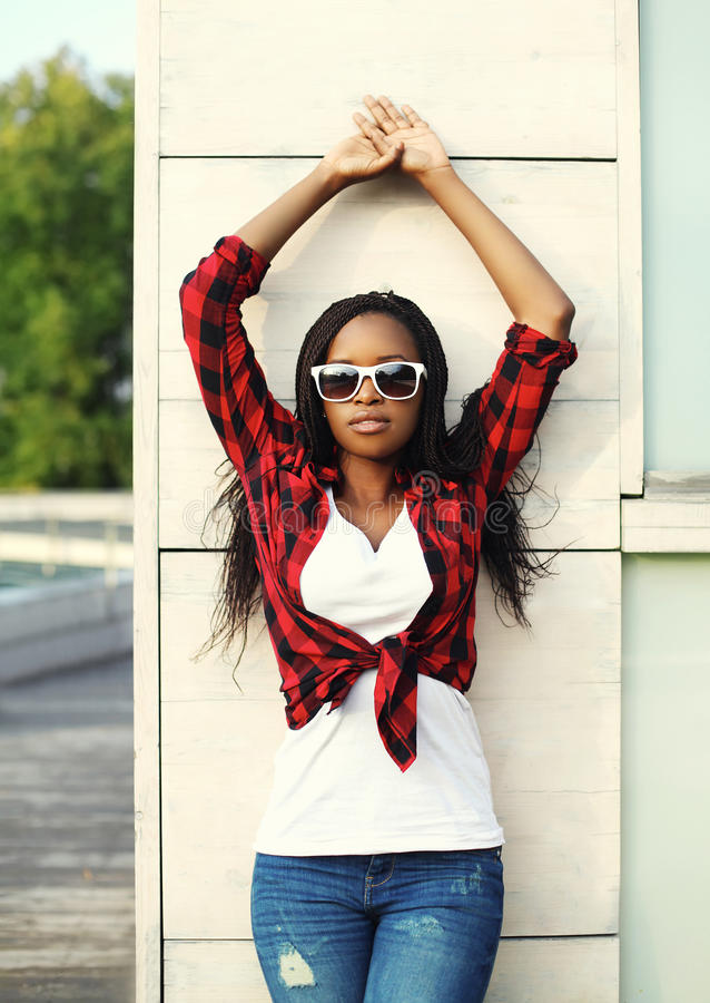 Arbeiten Sie die schöne afrikanische Frau um, die ein rotes kariertes Hemd und Sonnenbrille trägt lizenzfreies stockfoto