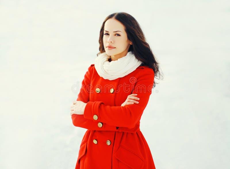 Arbeiten Sie die schöne junge Frau um, die eine rote Jacke im Winter trägt lizenzfreies stockfoto