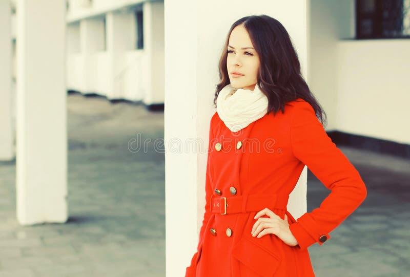 Arbeiten Sie die schöne junge Frau um, die eine rote Manteljacke und -schal im Winter trägt stockfoto