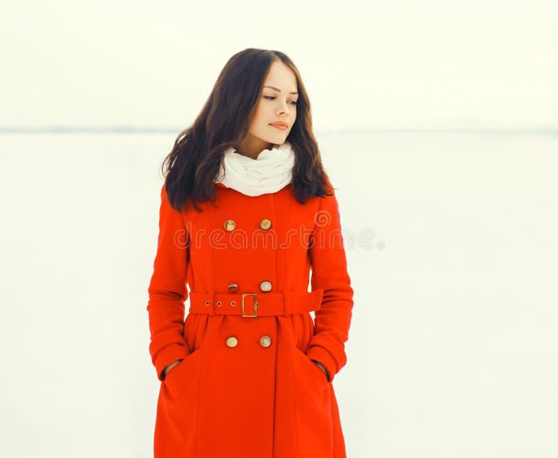 Arbeiten Sie die schöne junge Frau um, die rote Jacke auf dem Wintergebiet trägt lizenzfreie stockfotos