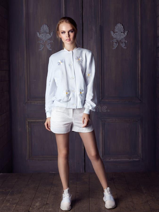 Arbeiten Sie die tragende weiße Jacke, kurze Hosen und Turnschuhe der Frau um, die gegen Tür aufwerfen lizenzfreie stockfotos