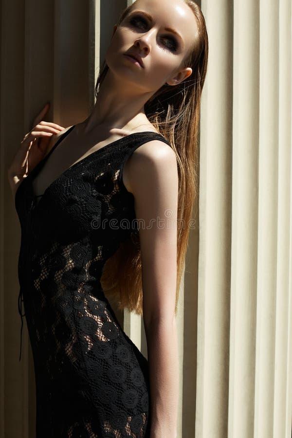Arbeiten Sie draußen Porträt des schönen Frauenbaumusters im schwarzen Spitzen- Luxuskleid um lizenzfreie stockfotografie