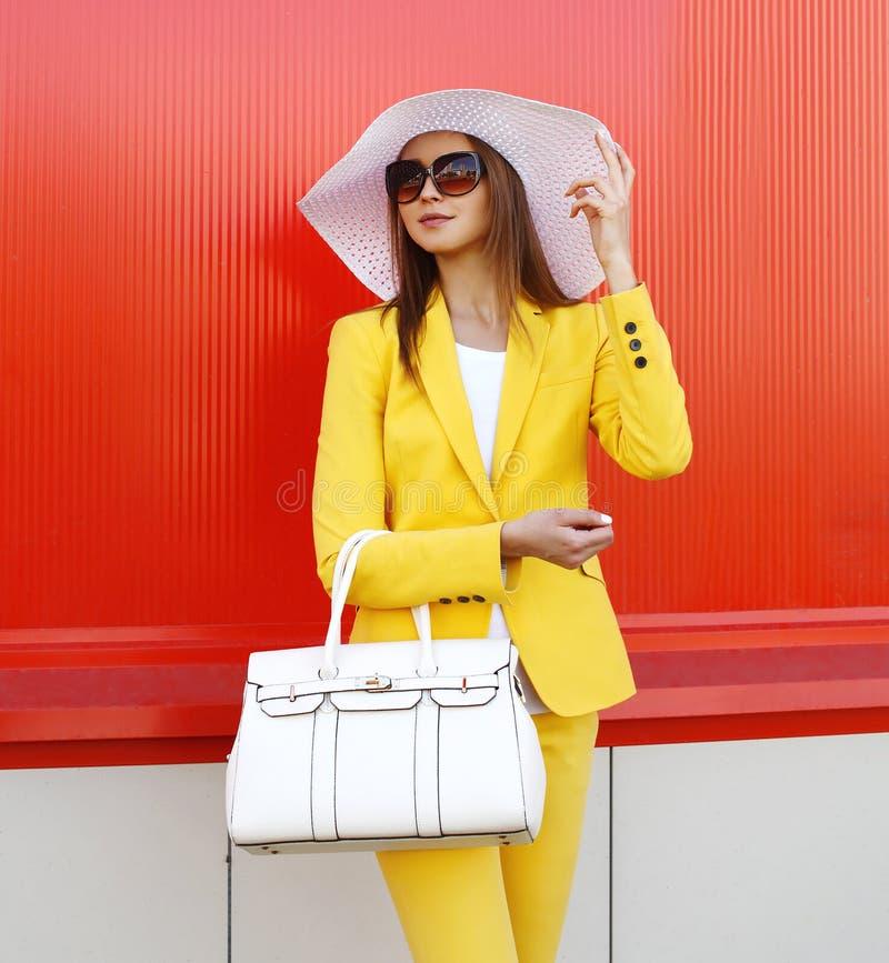 Arbeiten Sie eleganter Frau tragende Kleidung eines gelbe Anzugs, Strohhut um stockfoto