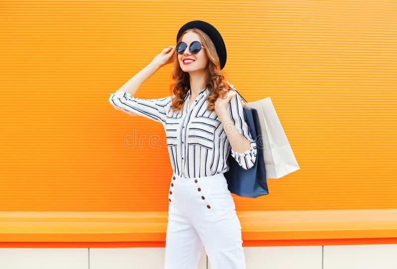 Arbeiten Sie elegantes junges lächelndes Frauenmodell mit den Einkaufstaschen um, die weiße Hosen eines schwarzen Hutes über bunt stockfoto