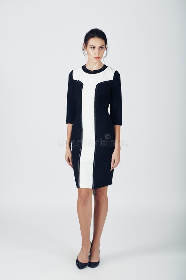 Arbeiten Sie Foto der jungen ausgezeichneten Frau in einem schwarzen Kleid um Mädchen lizenzfreie stockfotografie