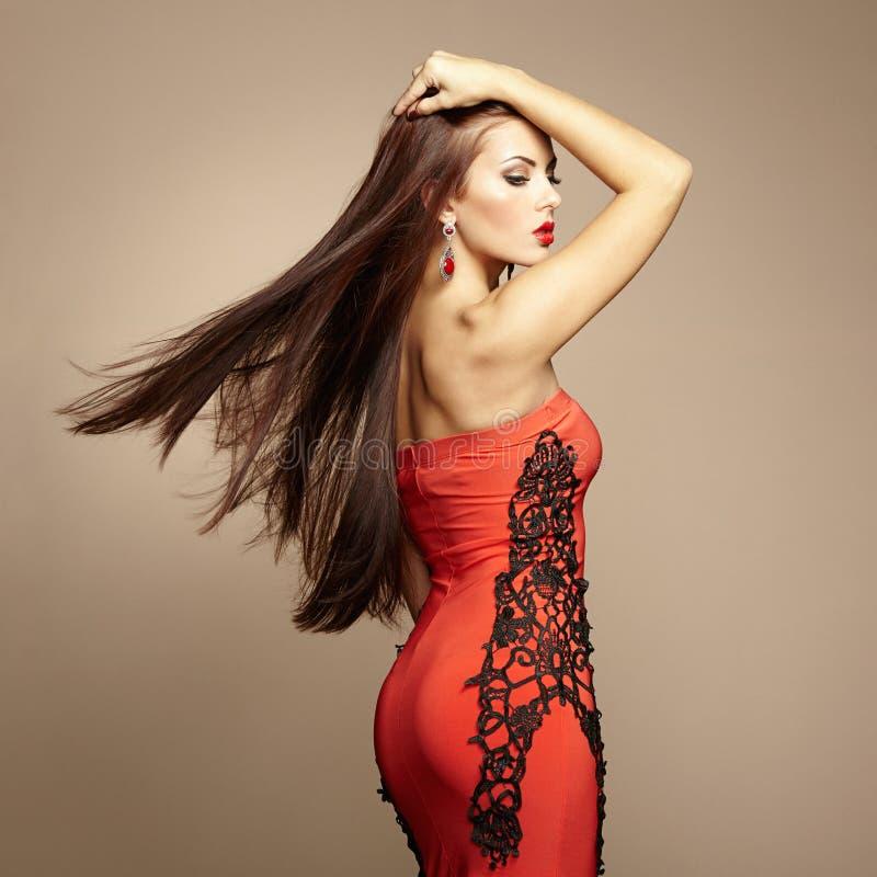 Arbeiten Sie Foto der jungen ausgezeichneten Frau im roten Kleid um lizenzfreie stockfotos