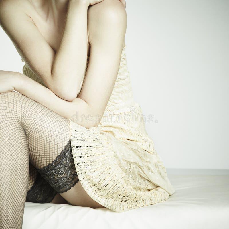 Arbeiten Sie Foto die junge sexuelle Frau um, die auf einem Sofa sitzt stockbild