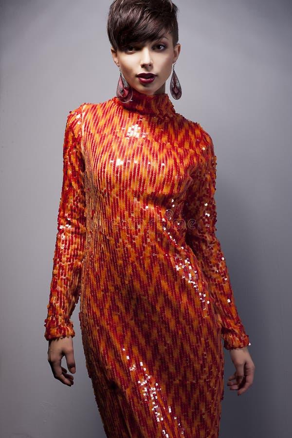 Arbeiten Sie Frau im roten Kleid mit Strass Aufstellung um lizenzfreies stockfoto