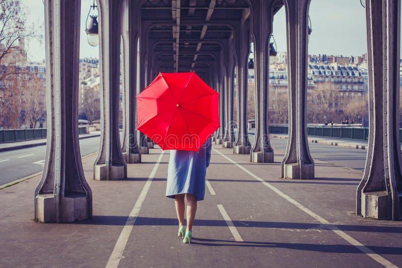 Arbeiten Sie Frau mit rotem Regenschirm in der Stadt um lizenzfreie stockfotografie