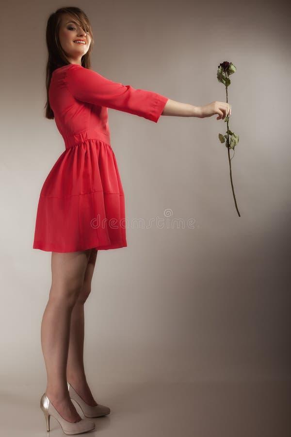 Arbeiten Sie Frau um, die jugendlich Mädchen im roten Kleid mit trockenem stieg lizenzfreies stockfoto