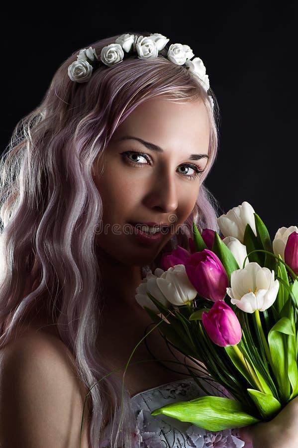 Arbeiten Sie Frauengesicht mit einem Blumenstrauß von Tulpen um stockbilder