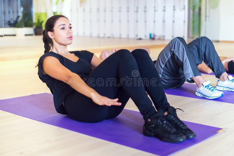 Arbeiten Sie Gruppe von Personen aus, die das Handeln ups Krisenyoga pilates Übungen der ABS Abdominal- in der Turnhalle oder im  stockfotos