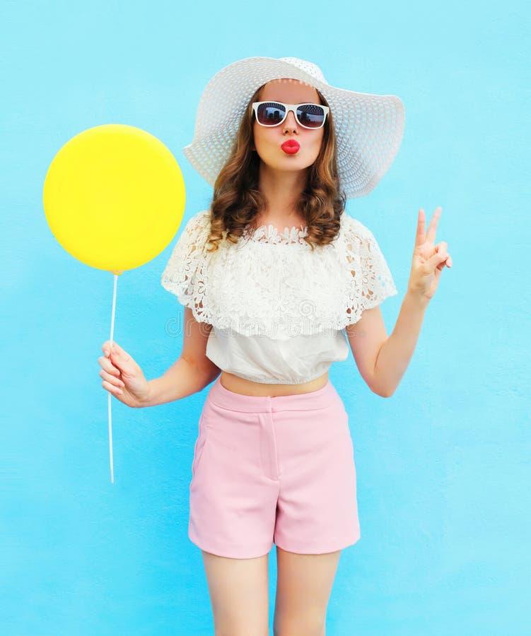 Arbeiten Sie hübsche Frau im Strohhut mit Luftballon über Blau um stockfotografie