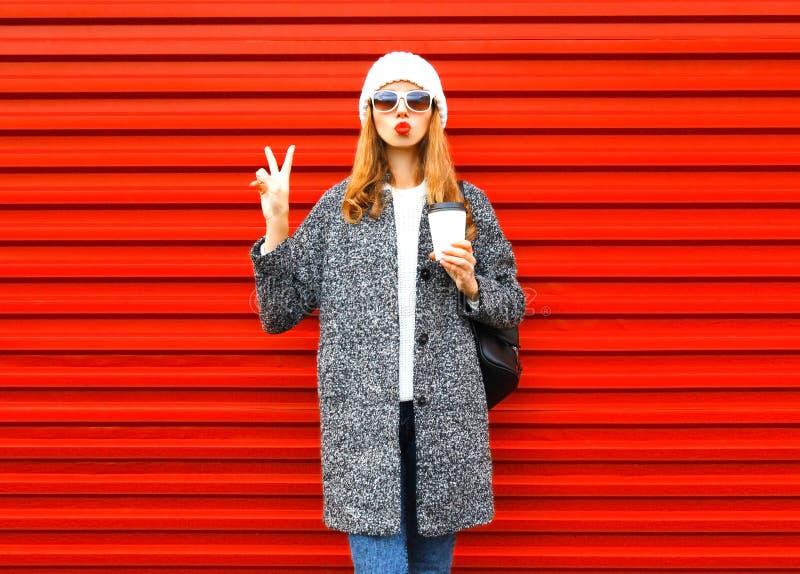 Arbeiten Sie hübsche Frau mit Kaffeetasse im Mantel um, der auf Rot aufwirft lizenzfreie stockbilder