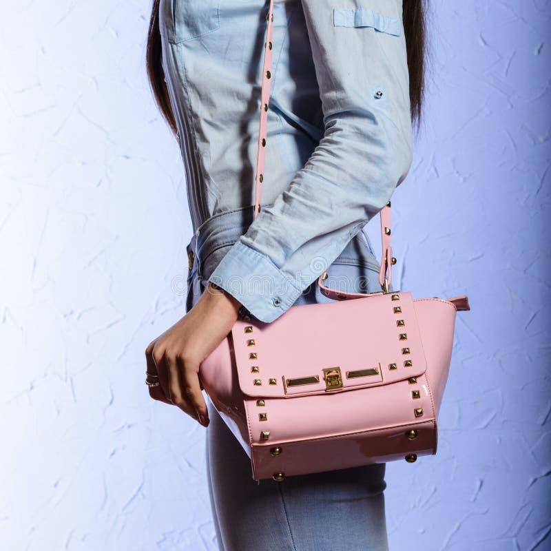 Arbeiten Sie junge Frau in den Jeans mit rosa Handtasche um lizenzfreies stockfoto