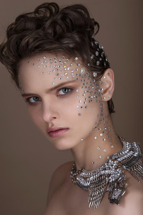 Arbeiten Sie junge Frau mit romantischem Make-up und schöner Frisur um Glänzender Leuchtmarker auf Haut Sexy Glanzlippen Dunkle A lizenzfreie stockfotos